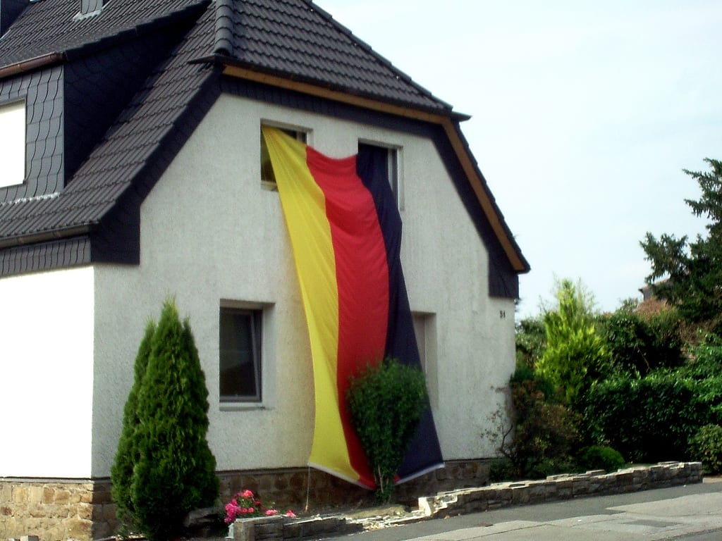 [house with German flag hanging from window]