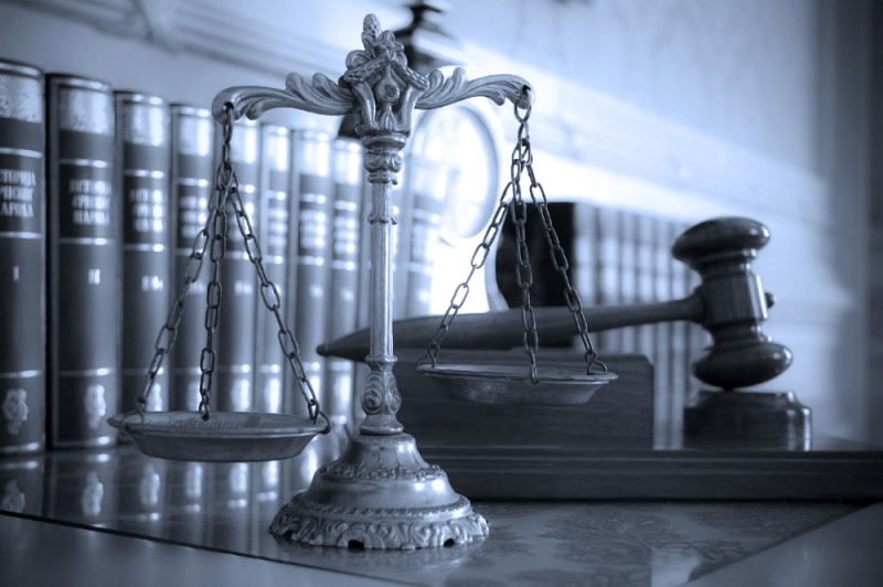 scales of justice in front of some law books