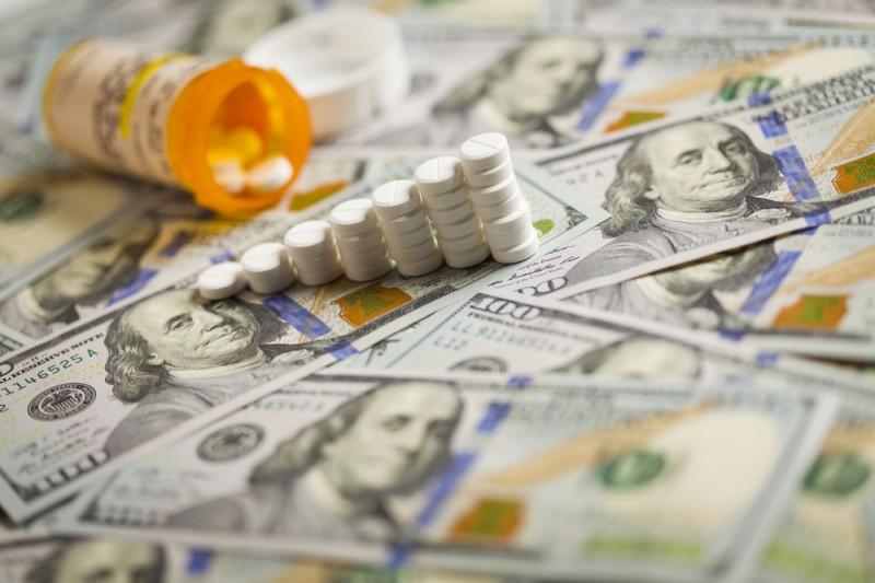 [prescription pills in a rising bar graph on $100 bills]