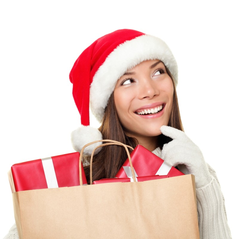 [Woman in Santa hat with bag of gifts]