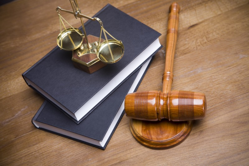 scales of justice on a law book next to a gavel
